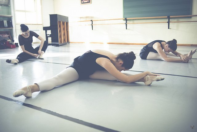ballet dancers stretching in the studio before class