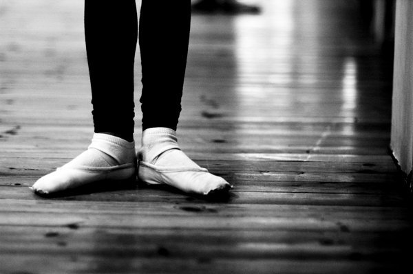 dancer in ballet slippers on wood floor