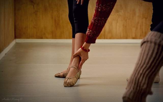ballet teacher positioning a foot to turn out