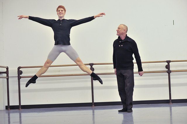 male ballet dancer jumping while instructor watches
