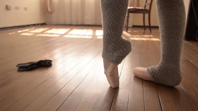 dancer's legs in pointe shoes with legwarmers