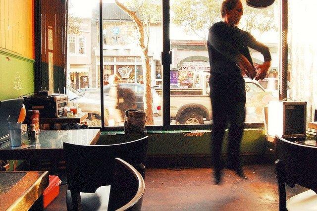 man in coffeeshop jumping