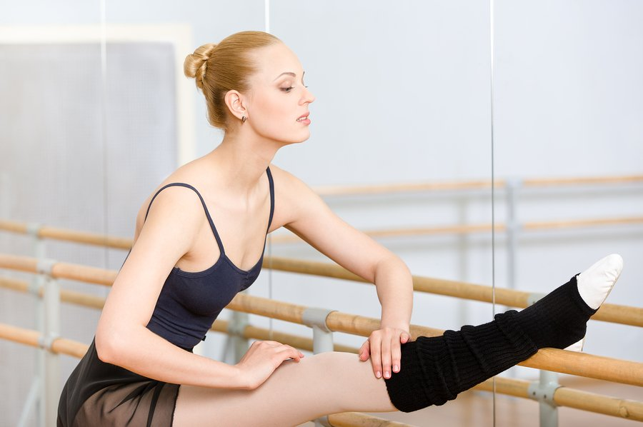 ballet dancer at barre with hair in a bun