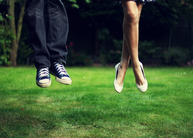 couple-jumping-green-grass