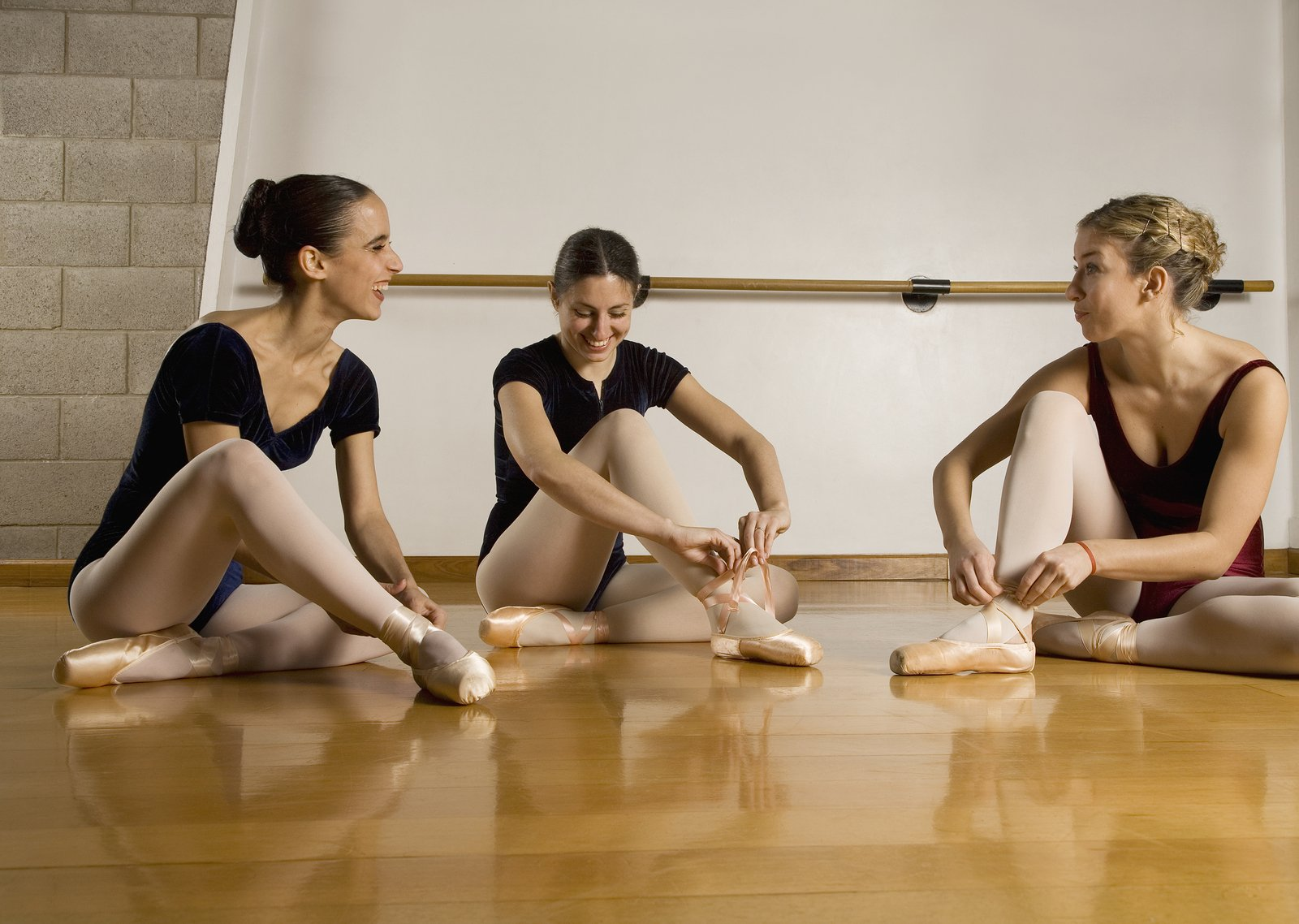 hispanic women ballet dancers talking while tying pointe shoes