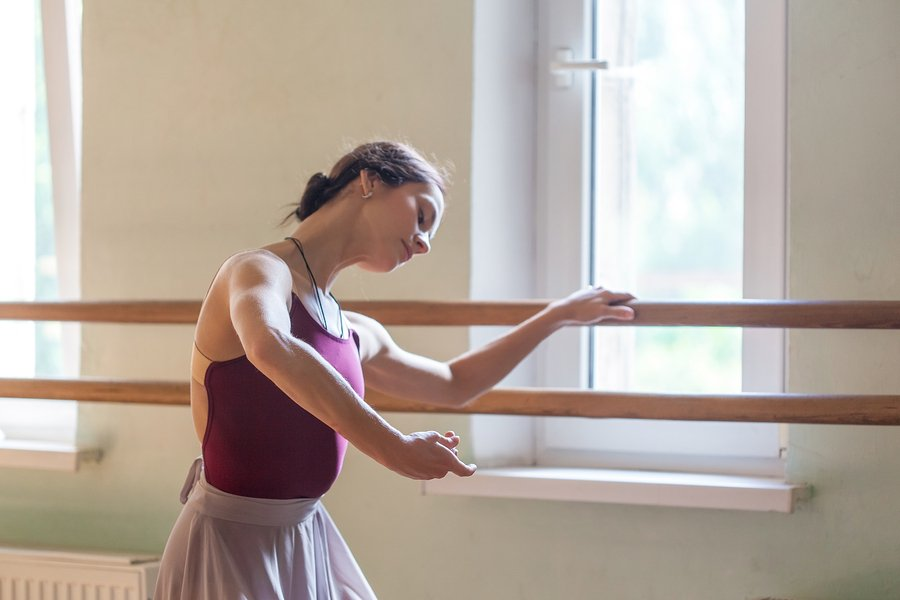 ballet dancer at barre with bent elbow