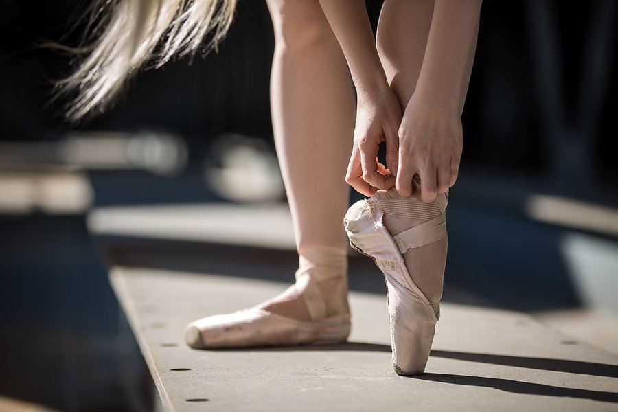 tying point shoes outdoors on sidewalk